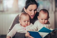 Charming mother showing images in a book to her cute twin babies. At home stock photo