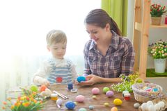 Charming mother and son celebrating Easter. Family celebrating Easter. Parent and kid play indoors. Decorated home and spring flow royalty free stock image