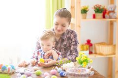 Charming mother and son celebrating Easter. Family celebrating Easter. Parent and kid play indoors. Decorated home and spring flow. Ers Royalty Free Stock Images
