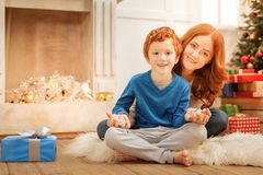 Charming mother and son holding their hands together. Family ties. Cheerful family sitting on the floor and looking into the camera with joyful smiles on their Stock Photography