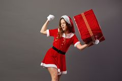 Charming mrs.Claus dressed in the red robe, Santa`s hat and white gloves holds in her hand the huge Christmas present on. The gray background stock photo