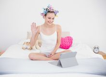 Charming natural brown haired woman in hair curlers chatting online with a tablet pc Royalty Free Stock Images