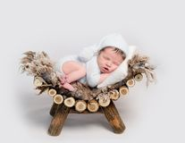 Newborn baby asleep on belly curled up on crib. Charming newborn baby asleep on belly curled up on wooden crib. Lovely newborn in grey soft outfit Royalty Free Stock Photo
