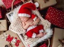 Charming newborn sleeping between christmas presents. Charming newborn sleeping with toy in cradle between christmas presents