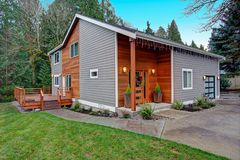 Charming newly renovated home exterior with mixed siding. Charming newly renovated home exterior, natural wood siding and grey siding help to encrease curb royalty free stock photos
