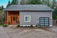 Charming newly renovated home exterior with mixed siding. Charming newly renovated home exterior, natural wood siding and grey siding create a beautiful curb royalty free stock photos