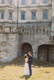 Charming newlywed bride and groom holding each other on lawn near beautiful ruined baroque palace Stock Photography