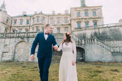 Charming newlywed bride and groom walking near beautiful ruined baroque palace Royalty Free Stock Image