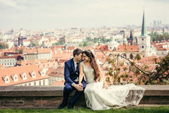 Charming newlywed couple is holding hands while sitting at the background of Prague panorama. Royalty Free Stock Image