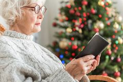 Charming old lady is reading Bible in holiday Stock Image