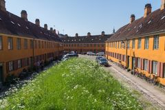 Charming old row houses in the district of Nyboder, Copenhagen, Denmark on a summer day. Old orange characteristic row houses in the historic district of former stock photo