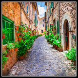 Charming old streets of Italian villages decorated with flowers royalty free stock photography