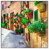 Charming old streets of Italy decorated with flowers. Stock Photography