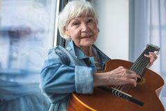 Charming Old Woman Playing Guitar Stock Photos