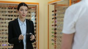 Charming optician selling glasses in optical shop stock video footage