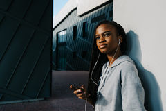 Charming outdoor portrait of the mysterious young afro-american girl in the earphones leaning on the wall. Charming outdoor portrait of the mysterious young Royalty Free Stock Images