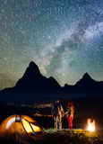 Charming pair holding hands, standing near tent and enjoying incredibly beautiful starry sky and Milky way Royalty Free Stock Image