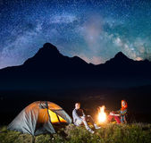 Charming pair tourists sitting by bonfire under incredibly beautiful starry sky, Milky way. Astrophotography. Charming pair tourists sitting by bonfire under stock images