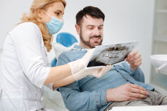 Charming patient happy seeing the progress. Nice results here. Lovely attentive prominent dentist holding a jaw scan and explaining positive tendencies to her Stock Photos