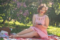 Charming pinup girl enjoys a rest and a picnic on the green summer grass. pretty vintage style caucasian woman spend vacantion on stock photos