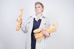 Charming pinup woman with short hair in a spring coat with polka dots posing with baguettes and enjoying them on a white backgroun. D in the Studio. plus size royalty free stock photo