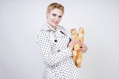 Charming pinup woman with short hair in a spring coat with polka dots posing with baguettes and enjoying them on a white backgroun. D in the Studio. plus size royalty free stock image