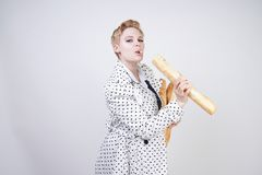 Charming pinup woman with short hair in a spring coat with polka dots posing with baguettes and enjoying them on a white backgroun. D in the Studio. plus size stock photography