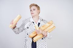 Charming pinup woman with short hair in a spring coat with polka dots posing with baguettes and enjoying them on a white backgroun. D in the Studio. plus size stock images
