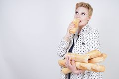 Charming pinup woman with short hair in a spring coat with polka dots posing with baguettes and enjoying them on a white backgroun. D in the Studio. plus size stock photos