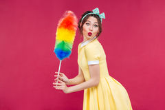 Charming playful pinup girl with colorful cleaning broom Stock Images