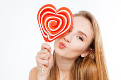 Charming playful woman with heart shaped lollipop sending a kiss Royalty Free Stock Photos