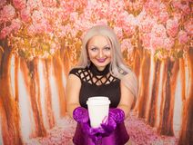 Charming plump blonde woman in a purple corset with long gloves holds a paper Cup of takeaway coffee with a mark of her lipstick k. Sexy blonde girl with plump royalty free stock photos