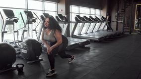 Charming plus size sportswoman stretching at the gym