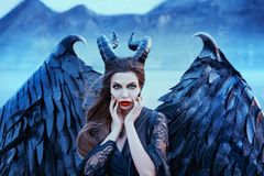Charming portrait of dark angel with sharp horns and claws on strong powerful wings, wicked witch in black lace dress royalty free stock image
