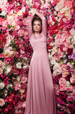 Charming portrait of young beautiful girl. In rosy skin-tight gown with dark smoky eyes and natural lipstick, on flowered background made of peony Royalty Free Stock Photo