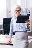 Charming positive aged businesswoman enjoying new gadget in the office stock photography
