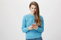 Charming positive fashion girl holding smartphone while looking ans smiling broadly at camera, typing something over. Gray background. Woman consults with girl stock photography