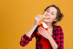 Charming positive young woman in checkered shirt eating fries Royalty Free Stock Photo