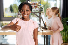 Charming pre-teen girl showing thumbs up. Best trip. Cheerful beautiful girl standing in the middle of a robotics exhibition hall and showing thumbs up being Royalty Free Stock Image