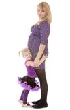 Charming pregnant mother with a young daughter who. Hugs her belly . on white Stock Photos