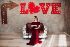 Charming pregnant woman in marsala dress posing on steps of house. royalty free stock photos