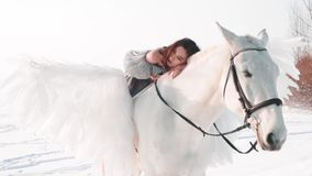 Charming pretty dark-haired lady in a long gray vintage dress with bare shoulders sits astride horse, tenderly lies on
