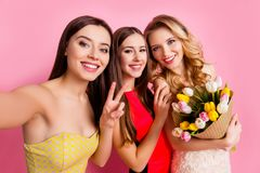 Charming, pretty girl making selfie photo on smart phone, front. Camera with her nice friends, showing two fingers, peace symbol,  girl hold bouquet of colorful Stock Images