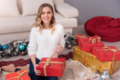Charming pretty woman unpacking her gift Royalty Free Stock Photography