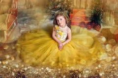 Charming princess girl in a yellow dress Stock Photos