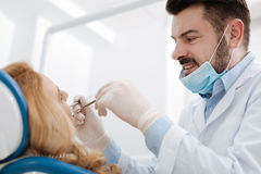 Charming professional dentist examining patients teeth. Special treatment for you. Distinguished skillful pleasant doctor running some tests while looking at the Stock Image