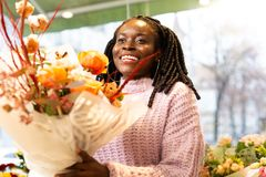 Charming professional florist demonstrating her creative bouquet. Cheerful emotions. Young designer expressing positivity while talking to visitors of her shop royalty free stock images