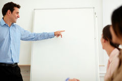 Charming professional man pointing at whiteboard Royalty Free Stock Images