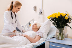 Charming qualified doctor giving her patient a nice prognosis. You will be dismissed soon. Wise prominent nice women paying aged lady a visit and telling her Royalty Free Stock Images