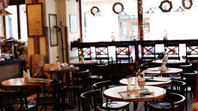 Charming quiet cafe with flowers on the tables and old wooden chairs made in aristocratic vintage style.
